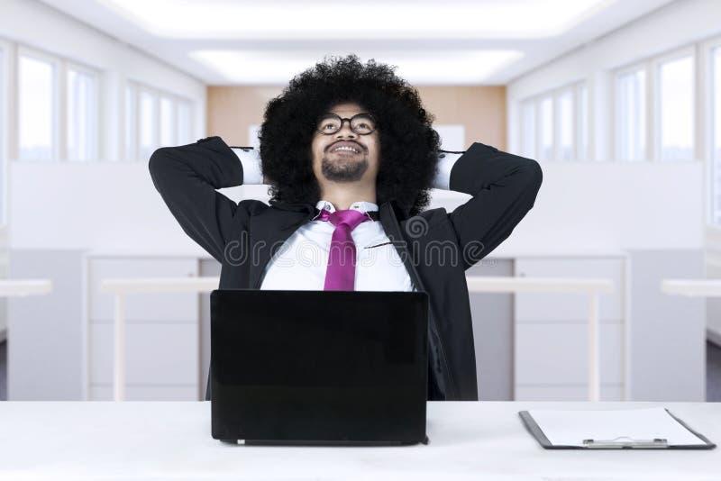 Het Afrikaanse zakenman ontspannen in bureau royalty-vrije stock afbeelding