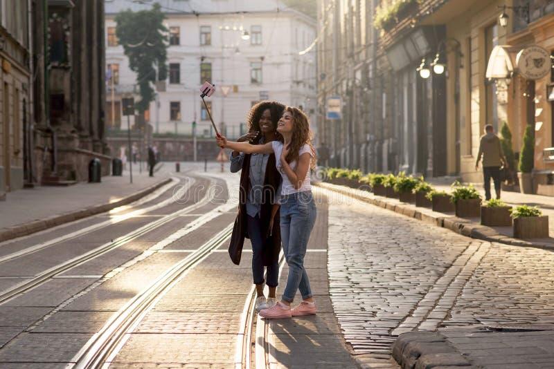 Het Afro-Amerikaanse brunette en haar blonde vrouwelijke vriend nemen selfies tijdens de zonsondergang stock afbeelding