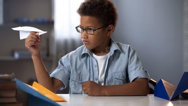 Het Afro-Amerikaanse jongen spelen met document vliegtuigen, toekomstige ingenieursontwerper, hobby stock fotografie