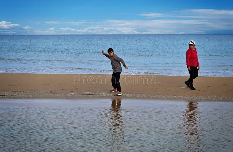 Het afromen van Stenen op het Strand stock foto's