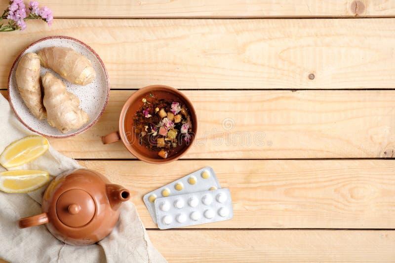 Het aftreksel, de pillen, theepot, citroen en gember de wortel op houten lijst, alternatief vlak geneeskundeconcept, leggen stijl stock fotografie