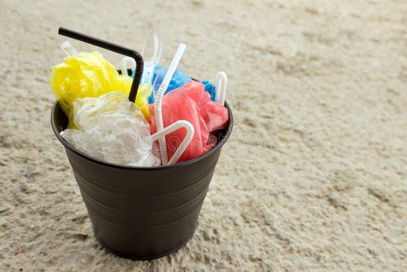 In het afval is de bak huisvuil dat van plastiek wordt gemaakt: zakken, beschikbare lepels, buizen voor cocktails royalty-vrije stock foto's
