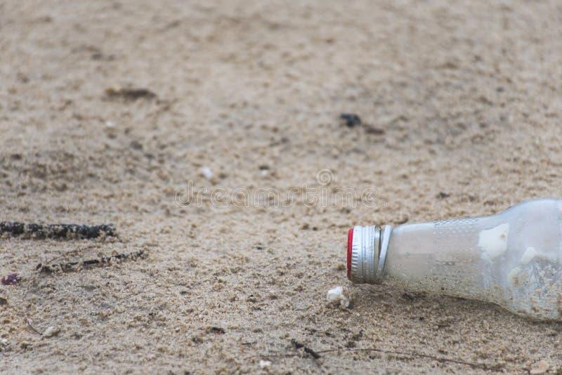 Het afval van de glasfles op de strandmilieuvervuiling die wordt gelaten vallen royalty-vrije stock foto's
