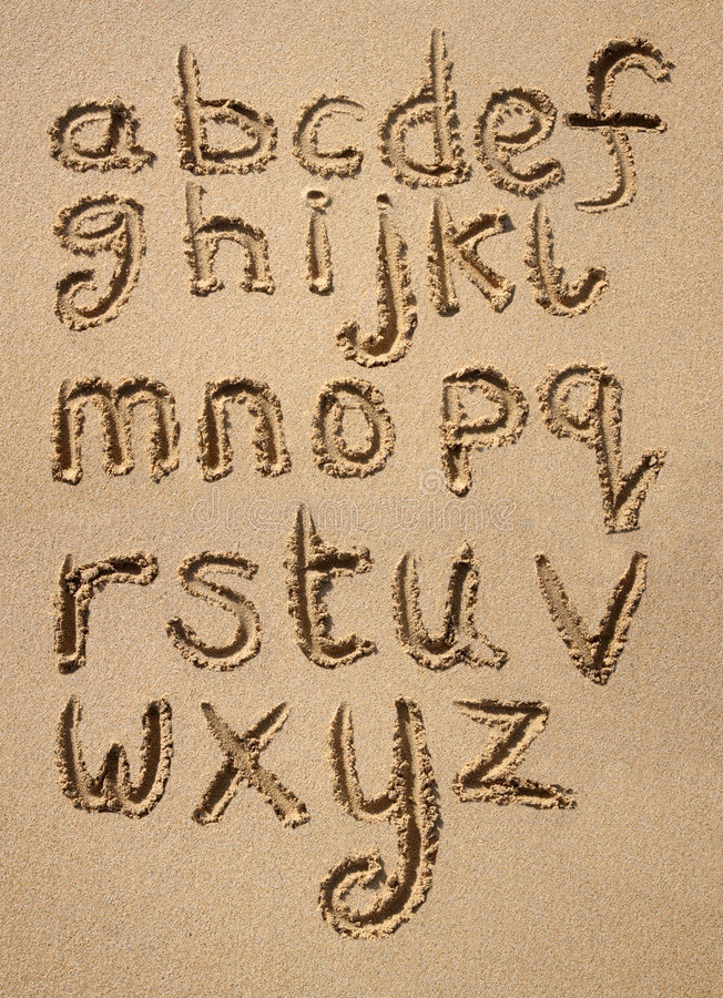 Het alfabet dat in zand wordt geschreven. stock fotografie