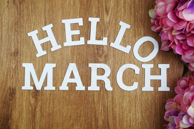 Het alfabetbrieven van Hello Maart met ruimteexemplaar en bloem op houten achtergrond stock afbeeldingen