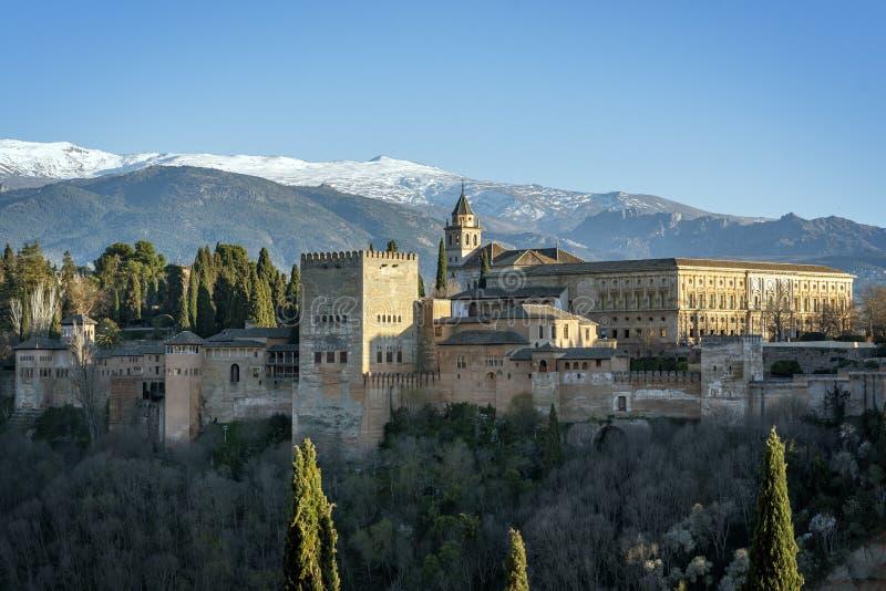 het Alhambra- en Charles V-paleis met het Nationaal Park van Sierra Nevada op de achtergrond, in de stad Granada, stock foto