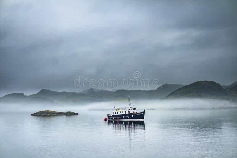 Het alleen boot drijven door in het mistige overzees in de Schotse hooglanden stock afbeeldingen