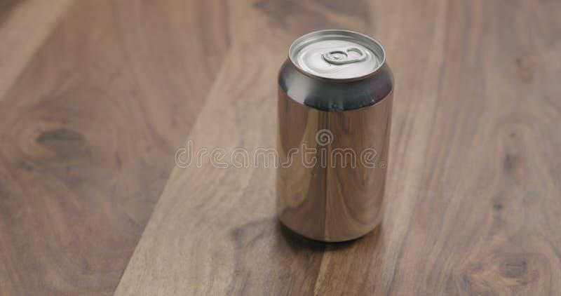 Het aluminium kan met soda op houten lijst drinken stock foto