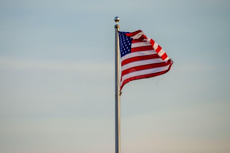 Het Amerikaanse vlag klappen in de wind bij dageraad royalty-vrije stock fotografie