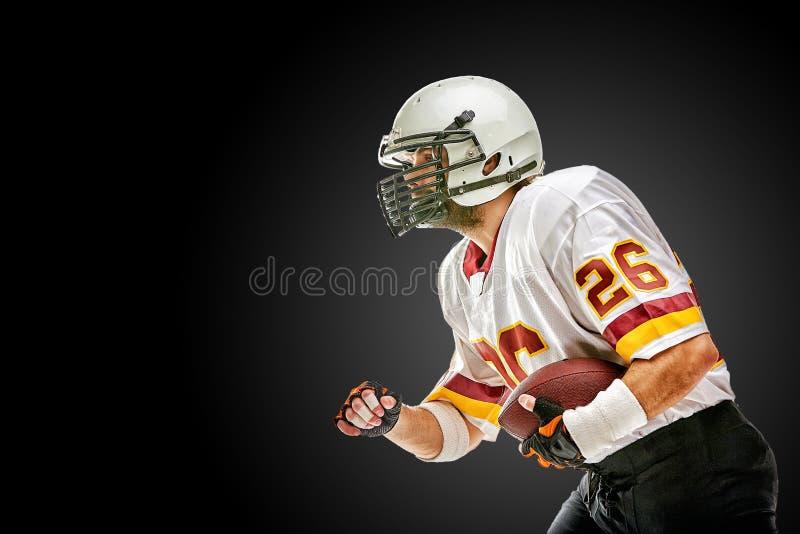 Het Amerikaanse voetbalster stellen met bal op zwarte achtergrond Vierkant Formaat Concepten Amerikaanse voetbal, portret royalty-vrije stock afbeelding