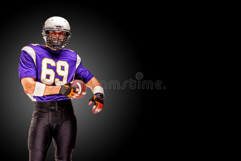 Het Amerikaanse voetbalster stellen met bal op zwarte achtergrond Vierkant Formaat Concepten Amerikaanse voetbal, portret stock afbeeldingen