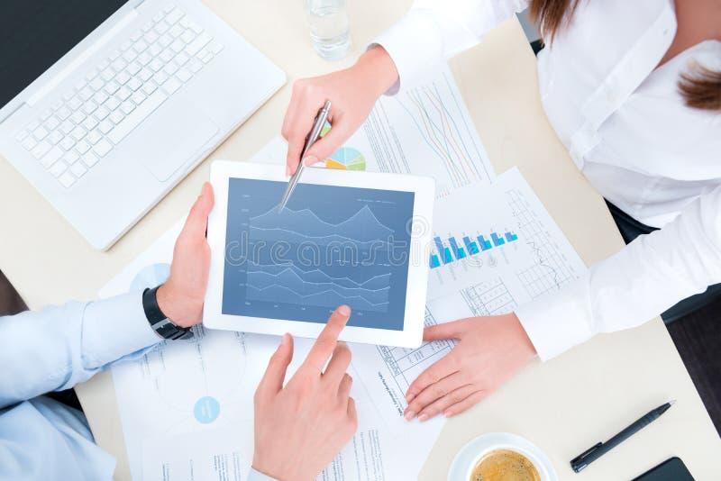 Het analyseren van financiële grafiek op appel ipad stock afbeelding