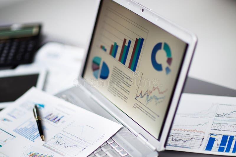 Het analyseren van investeringsgrafieken met laptop stock foto