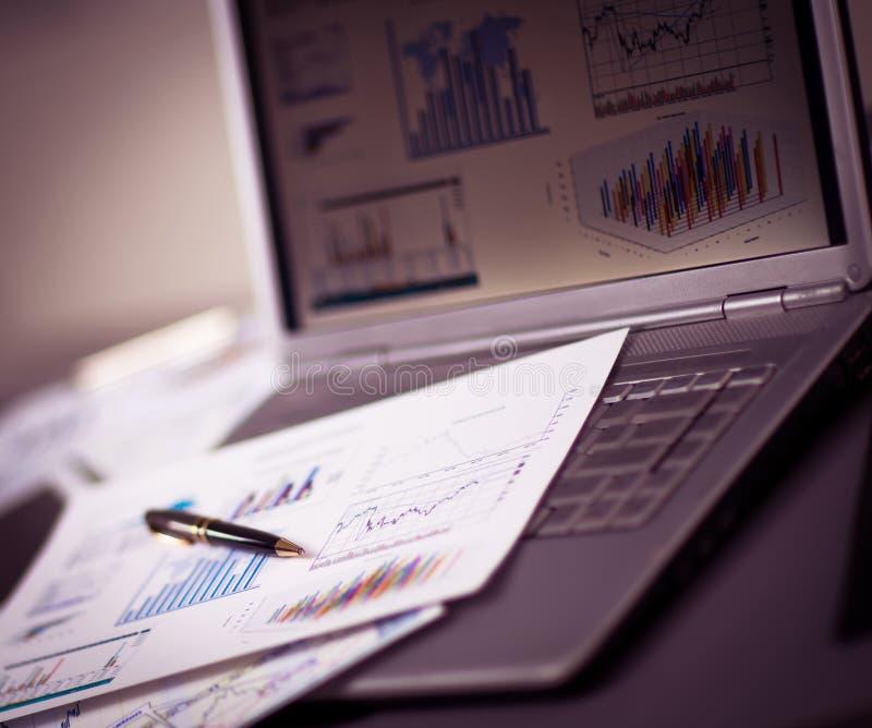 Het analyseren van investeringsgrafieken met laptop stock fotografie