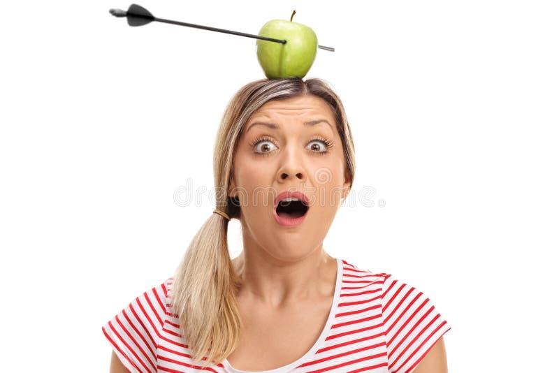 Het angst aangejaagde jonge vrouw stellen met appel die door een pijl wordt doordrongen royalty-vrije stock afbeeldingen