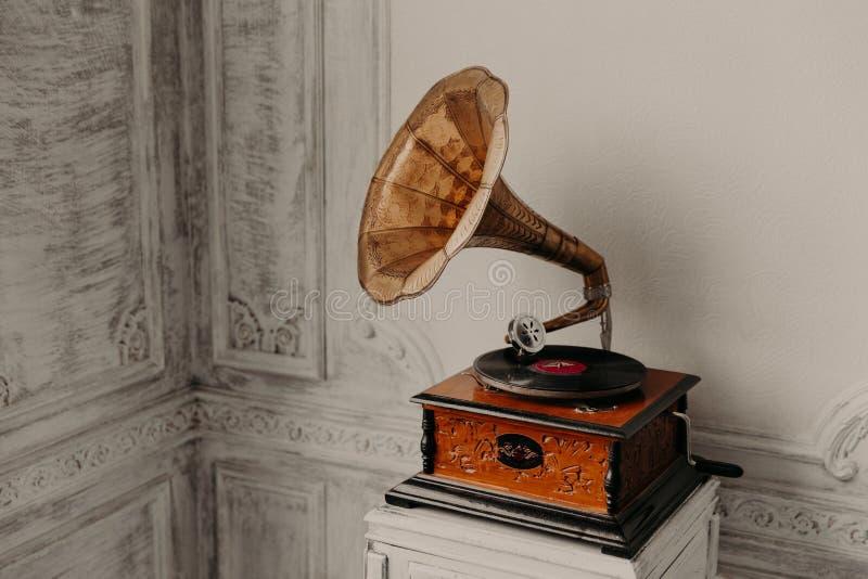 Het apparaat van de muziek Oude grammofoon met plaat of vinylschijf op houten doos Antieke messingsplatenspeler Grammofoon met ho stock foto's