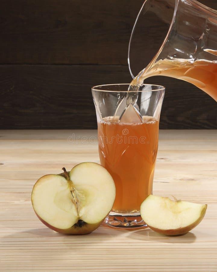 Het appelsap van rijpe en sappige appelen wordt gegoten in een glas Dichtbij het glas lig plakken van verse appelen Close-up stock afbeeldingen