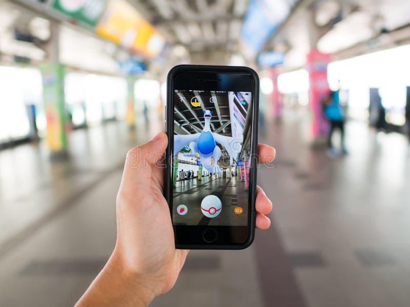 Het Apple iPhone 7 in één hand wordt gehouden die het zijn scherm met Pokemon tonen gaat toepassing die stock foto's