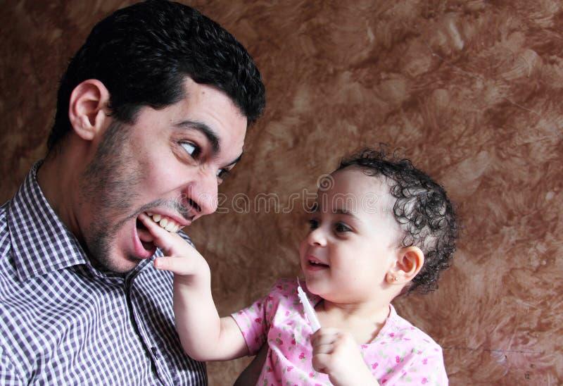 Het Arabische Egyptische babymeisje spelen met haar vader stock afbeelding