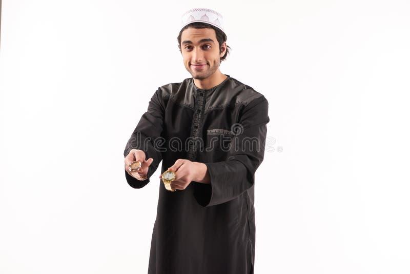 Het Arabische mannetje in etnische kleding biedt gouden horloge aan stock afbeelding