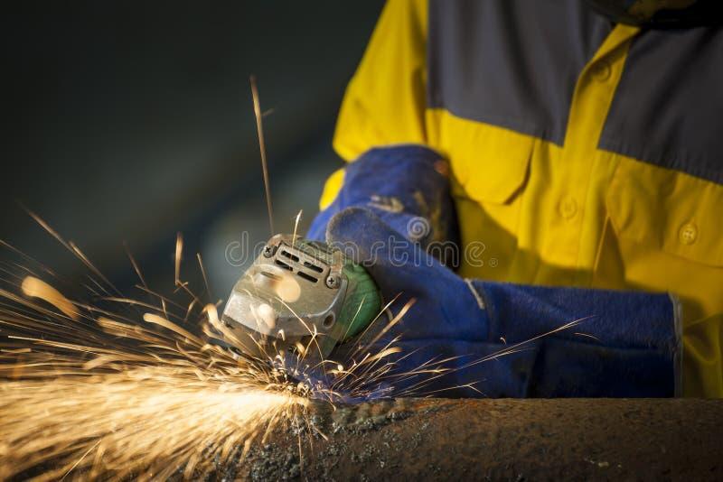 Het arbeiders malende metaal in productieinstallatie, vonken het vliegen stock afbeeldingen