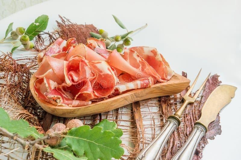 Het aroma van ham en kruiden, dat dun op een witte lijst met brood antiek Bestek en rode wijn wordt gesneden stock fotografie