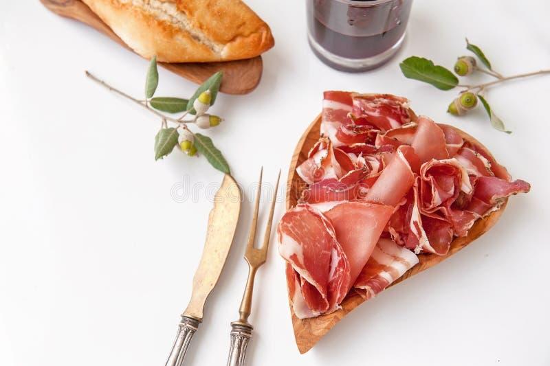 Het aroma van ham en kruiden, op een witte lijst met brood en antiek Bestek dun wordt gesneden dat royalty-vrije stock afbeelding