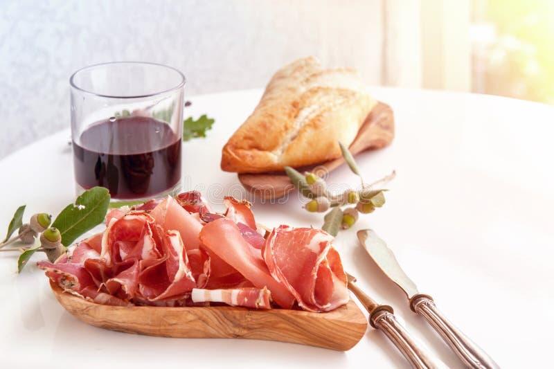Het aroma van ham en kruiden, op een witte lijst met brood en antiek Bestek dun wordt gesneden dat royalty-vrije stock fotografie