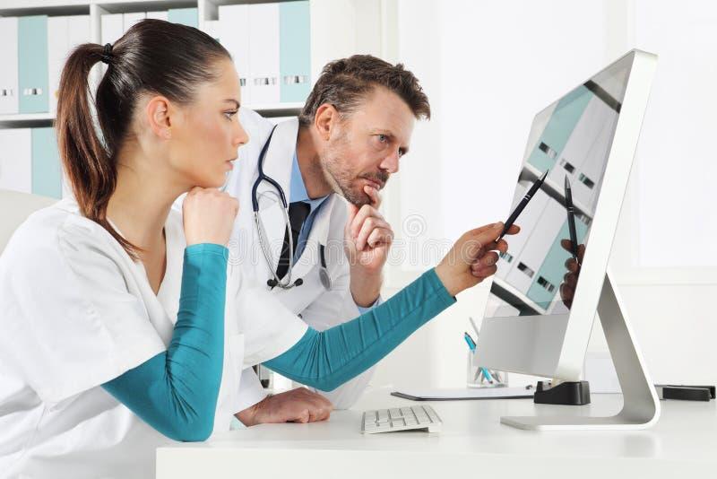 Het artsengebruik de computer met verpleegster, concept medisch raadpleegt stock afbeeldingen