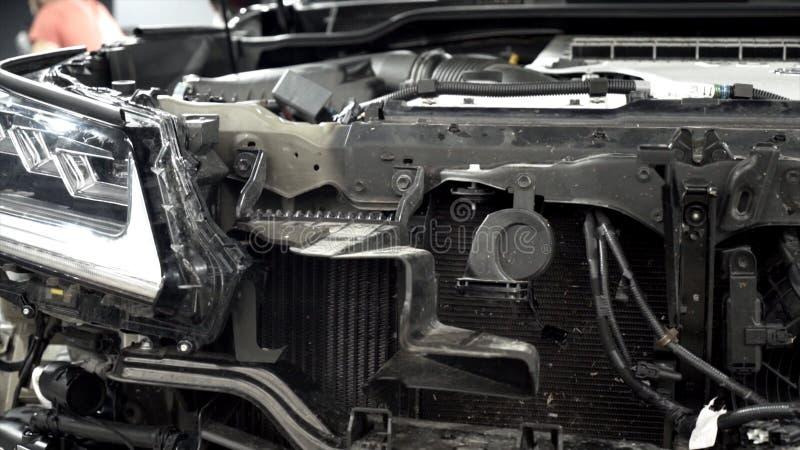 Het assembleren van kap van auto in automobielinstallatie actie Close-up van details van voorzijde van auto op achtergrond van we royalty-vrije stock foto