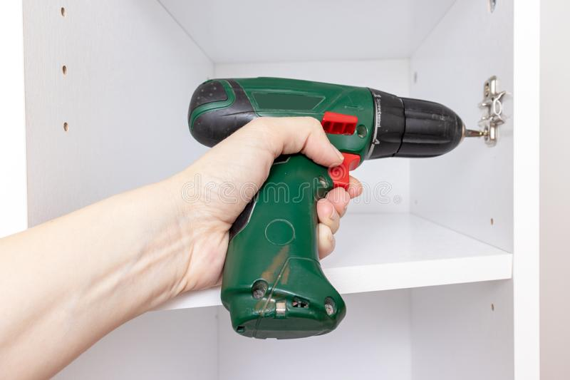 Het assembleren van meubilair van spaanplaat, die een draadloze schroevedraaier gebruiken, sluit omhoog stock foto