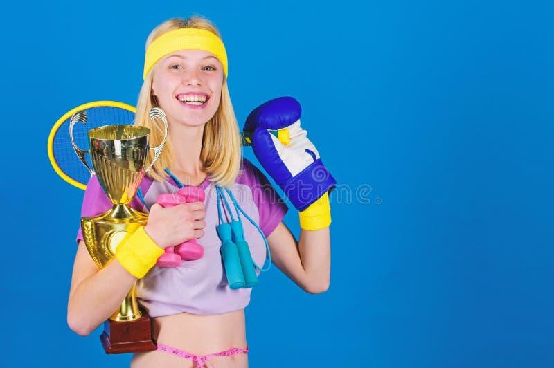 Het assortiment van de sportwinkel De greep gouden drinkbeker van de meisjes succesvolle moderne vrouw sportkampioen en materiaal stock afbeelding