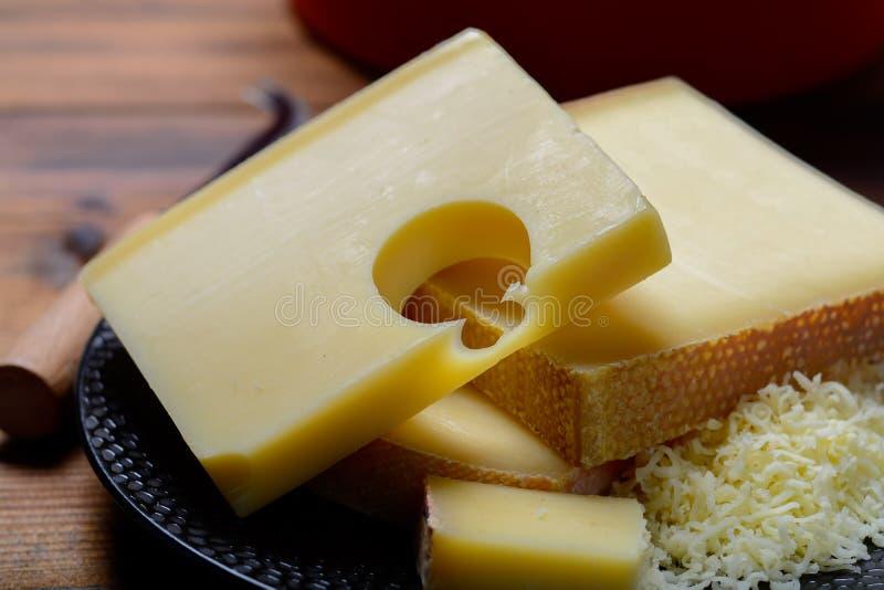 Het assortiment van Emmentalersemmentaler of Emmentaler medium-hard kaas met ronde gaten, Gruyère, appenzeller en raclette gebrui royalty-vrije stock afbeelding