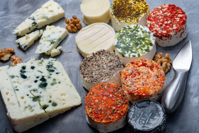 Het assortiment van Franse verse witte zachte geitkazen met het verschillende smaken bedekken maakte met kruiden, paprika, Indisc royalty-vrije stock foto