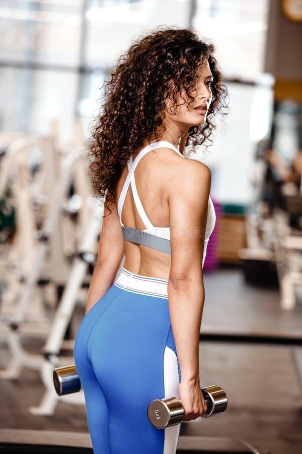 Het Atletic donker-haar het krullende meisje gekleed in een sportkleding zich met de domoren in haar bevindt dient de moderne gym royalty-vrije stock afbeeldingen
