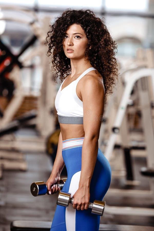 Het Atletic donker-haar het krullende meisje gekleed in een sportkleding zich met de domoren in haar bevindt dient de moderne gym royalty-vrije stock foto