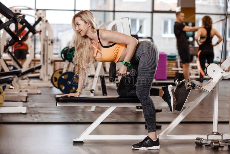 Het atletische blonde meisje met lang haar gekleed in een sportkleding doet oefening op de bank met binnen domoren voor triceps stock foto
