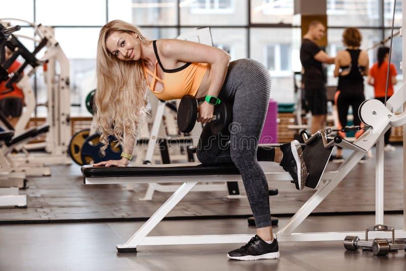 Het atletische blonde meisje met lang haar gekleed in een sportkleding doet oefening op de bank met binnen domoren voor triceps stock afbeelding
