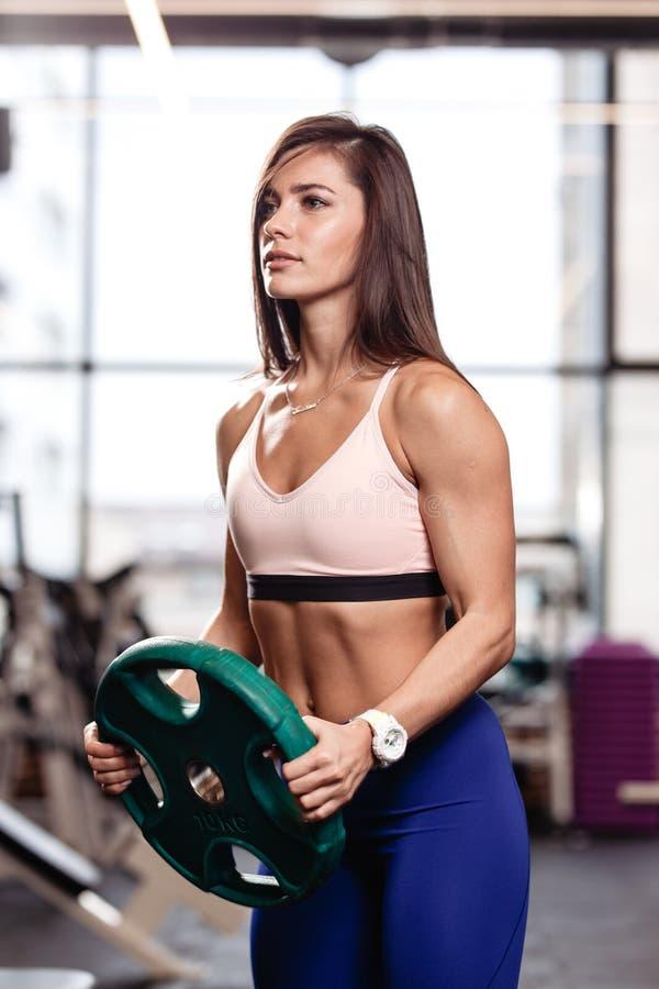 Het atletische jonge donkerbruine meisje houdt een zware plaat in haar de moderne gymnastiek indient royalty-vrije stock foto's