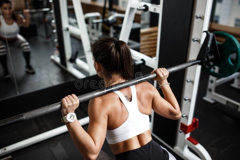 Het atletische jonge meisje kleedde zich in sportkledingshurkzit met een barbell in de moderne gymnastiek royalty-vrije stock afbeelding