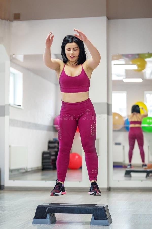 Het atletische jonge meisje praktizeren op stepper in de gymnastiek Het concept sporten, een gezonde levensstijl, verliezend gewi royalty-vrije stock foto's