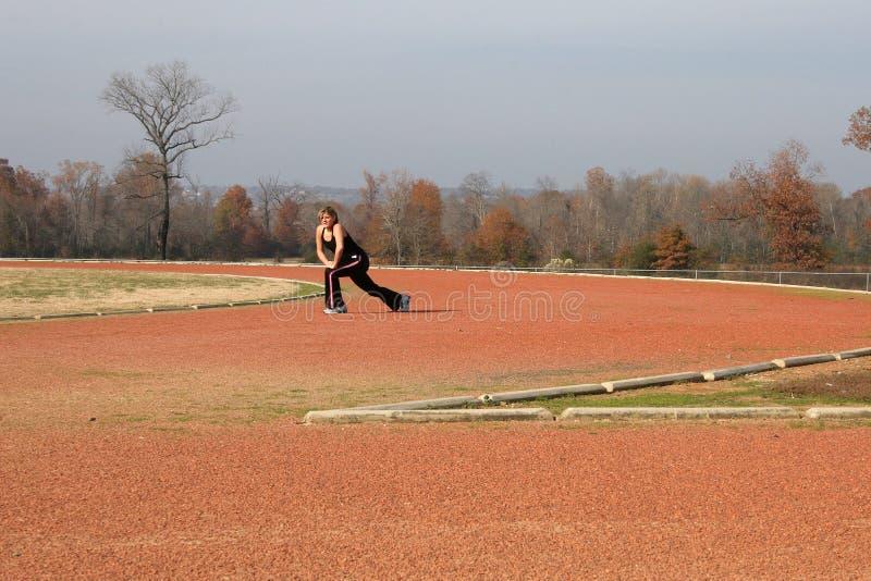 Het atletische Jonge Uitrekken van de Vrouw zich bij het Spoor stock foto's