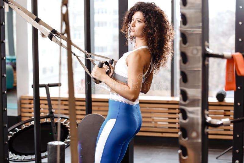 Het atletische krullende meisje gekleed in een sportkleding heeft een TRX-training in het moderne gymnastiekhoogtepunt van zonlic royalty-vrije stock foto