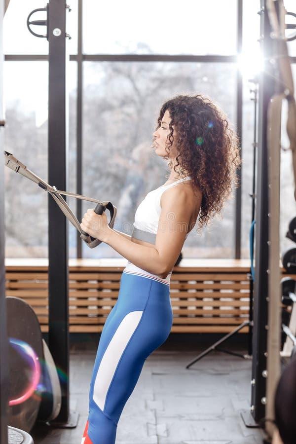 Het atletische krullende meisje gekleed in een sportkleding heeft een TRX-training in het moderne gymnastiekhoogtepunt van zonlic royalty-vrije stock afbeeldingen