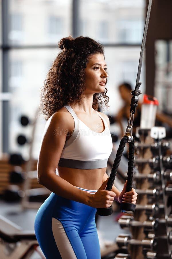 Het atletische krullende meisje heeft een TRX-training in het moderne gymnastiekhoogtepunt van zonlicht royalty-vrije stock foto's