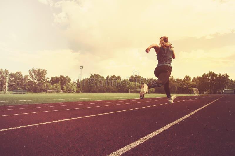 het atletische meisje stelt atletisch meisje in werking loopt bij stadion stock fotografie