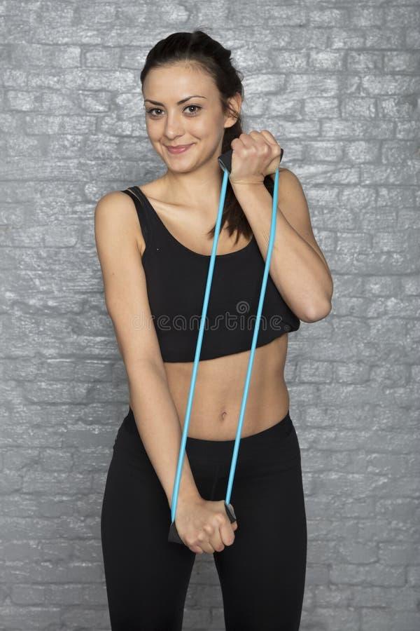 Het atletische meisje voert oefeningen met rubber uit stock foto's