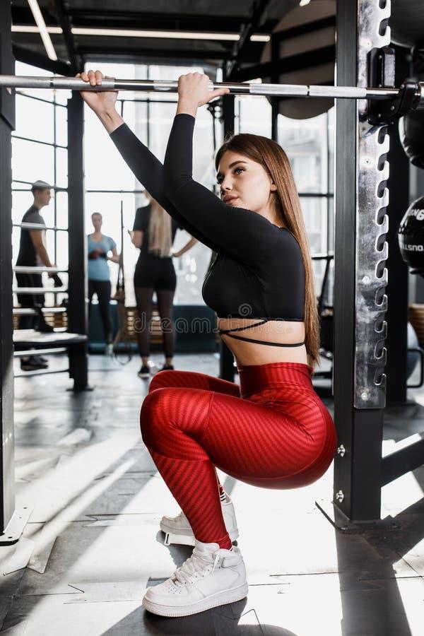 Het atletische mooie meisje in modieuze heldere sportenkleren stelt naast de rekstok in de moderne gymnastiek royalty-vrije stock fotografie