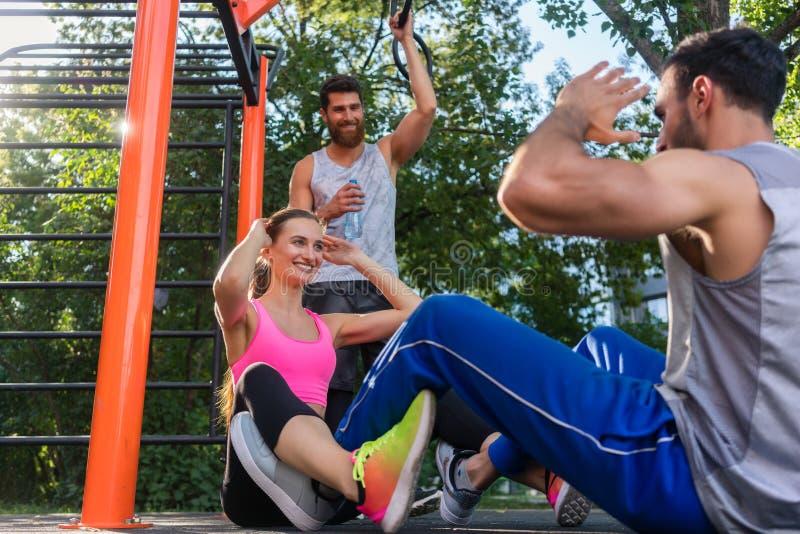 Het atletische paar die handen slaan terwijl het doen kraakt face to face royalty-vrije stock foto