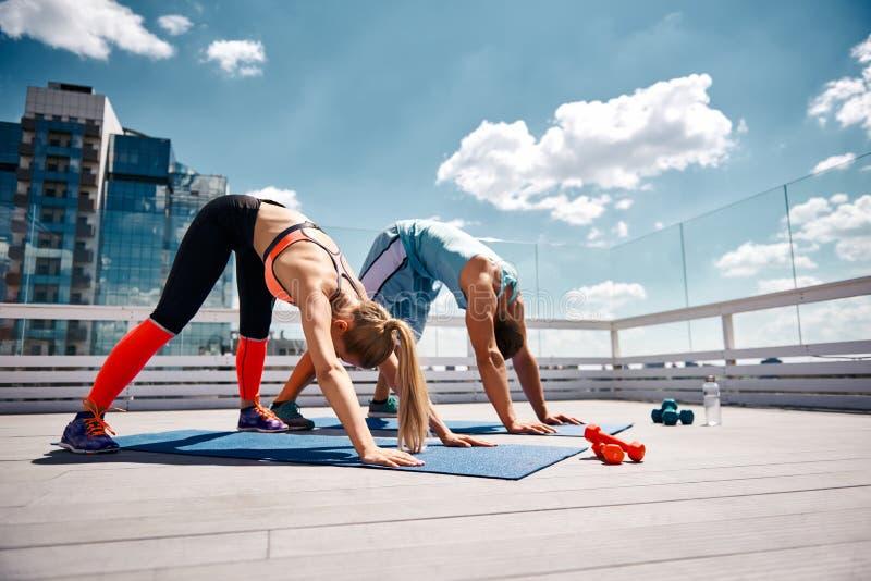 Het atletische paar oefent samen op dak uit stock foto's